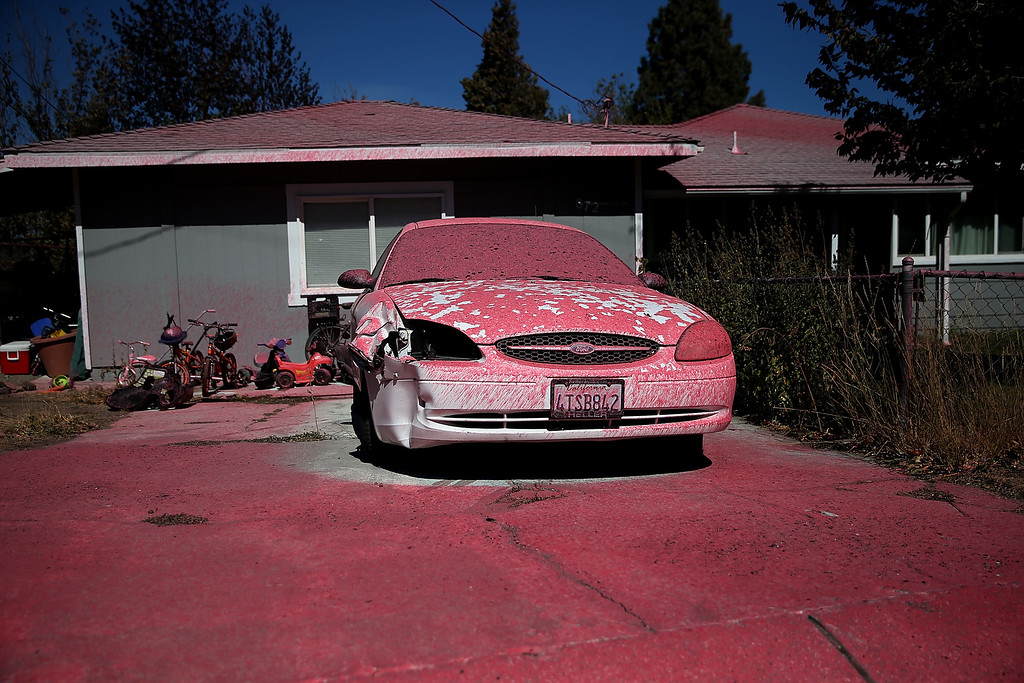. Foscheck fire retardant covers a car in front of a home after a wildfire on September 16, 2014 in Weed, California. A fast moving wildfire fueled by high winds ripped through the town of Weed on the afternoon of September 15, burning 100 structures including the high school and lumber mill.  (Photo by Justin Sullivan/Getty Images)
