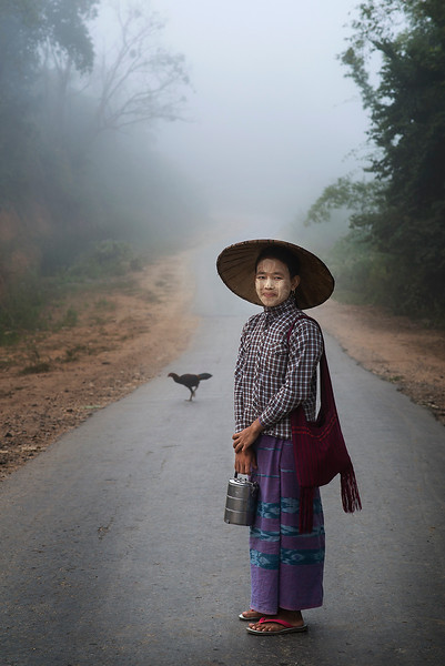 A young worker heads of to the fields with her warm lunch in a flask.  Myanmar 2017.