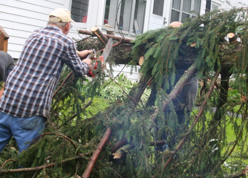 . John Chmielewski uses a chainsaw to clear a fallen tree at a home at the intersection of West Main Street and Station Street in Verona following an early morning storm on Wednesday, June 18, 2014. JOHN HAEGER @ONEIDAPHOTO ON TWITTER/ONEIDA DAILY DISPATCH