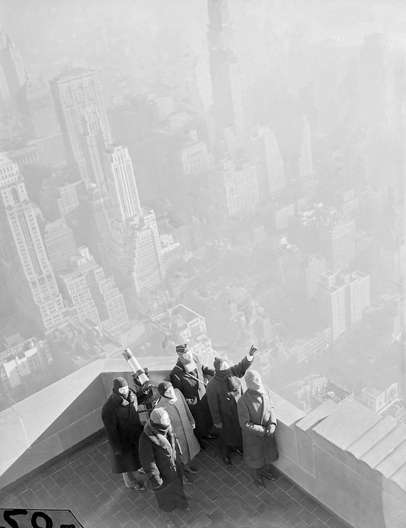 """. Heavily-wrapped American Legion volunteers kept a cold vigil atop the Empire State Building, watching for \""""enemy bombers\"""" in a test of New York and New England defense preparations in New York, Jan. 21, 1941. As planes sent from army fields were sighted, their number, speed and direction were reported to an army information center for analysis as to course.(AP Photo/John Lindsay)"""