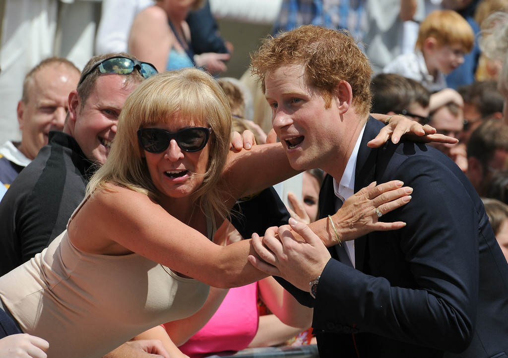 . WEST TANFIELD, ENGLAND - JULY 5:  Prince Harry is hugged by a member of the crowd prior the start of the Tour de France on July 5, 2014 at West Tanfield, Yorkshire, England.  (Photo by Anna Gowthorpe - WPA Pool/Getty Images)
