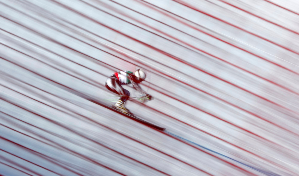 Description of . The long time exposed photo taken through a safety fence shows an unidentified skier during the first run of the men\'s giant slalom  at the Alpine skiing world championships in Schladming, Austria, Friday, Feb. 15, 2013. (AP Photo/Matthias Schrader)