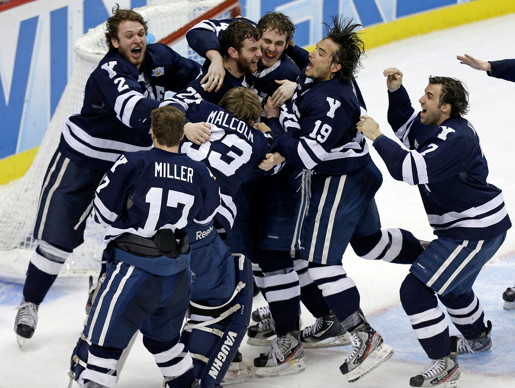 . Yale goalie Jeff Malcolm (33) is swarmed by teammates after shutting out Quinnipiac  and leading the Bulldogs to a 4-0 win in the NCAA men\'s college hockey national championship game in Pittsburgh Saturday, April 13, 2013.  (AP Photo/Gene Puskar)