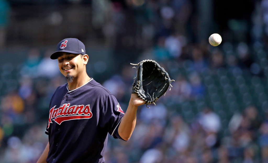 . Cleveland Indians starting pitcher Carlos Carrasco reaches for the ball against the Seattle Mariners in the first inning of a baseball game Saturday, Sept. 23, 2017, in Seattle. (AP Photo/Elaine Thompson)
