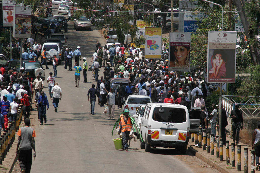 . Crowds gather outside the Westgate Mall, an upscale shopping mall  in Nairobi, Kenya Saturday Sept. 21 2013, where shooting erupted when armed men staged an attack. (AP Photo/Jason Straziuso)