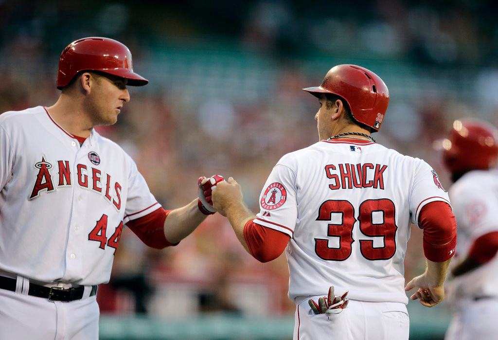 . Los Angeles Angels\' J.B. Shuck, right, is greeted by Mark Trumbo after scoring on a sacrifice hit by Howie Kendrick in the first inning Monday. (AP Photo/Jae C. Hong)