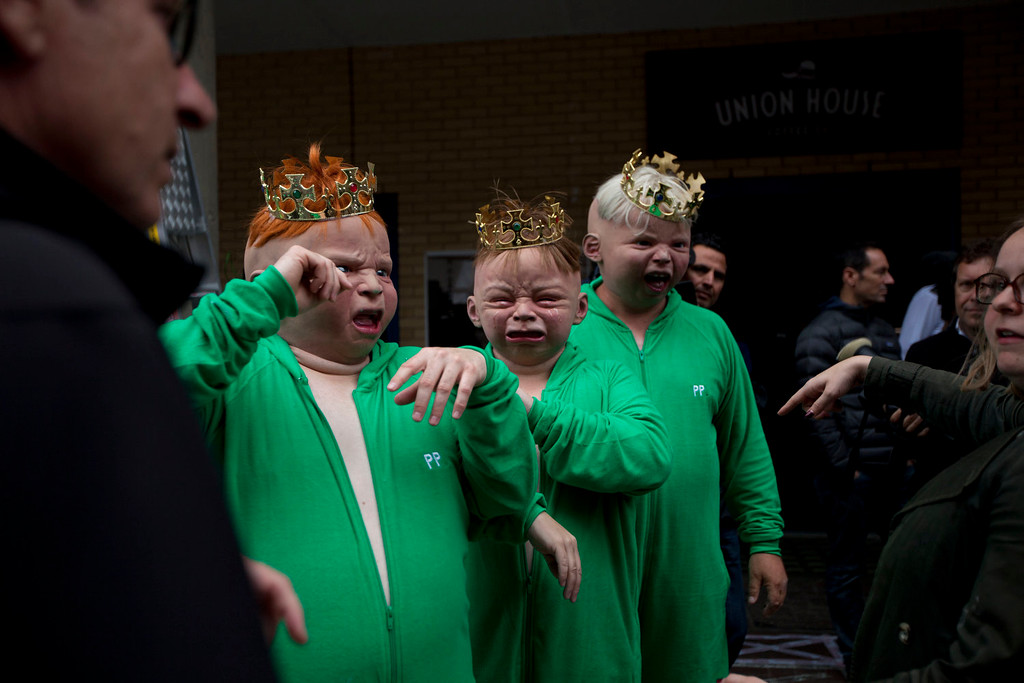 . Representatives from a betting company wear baby masks as they perform a publicity stunt outside St. Mary\'s Hospital in London, Friday, July 12, 2013. Media are preparing for royal-mania as Britain\'s Kate, Duchess of Cambridge is expected to give birth to the new third-in-line to the throne in mid-July, at the Lindo Wing. Cameras from all over the world are set to be jostling outside for an exclusive first glimpse of Britain\'s Prince William and the Duchess of Cambridge\'s first child.  (AP Photo/Matt Dunham)