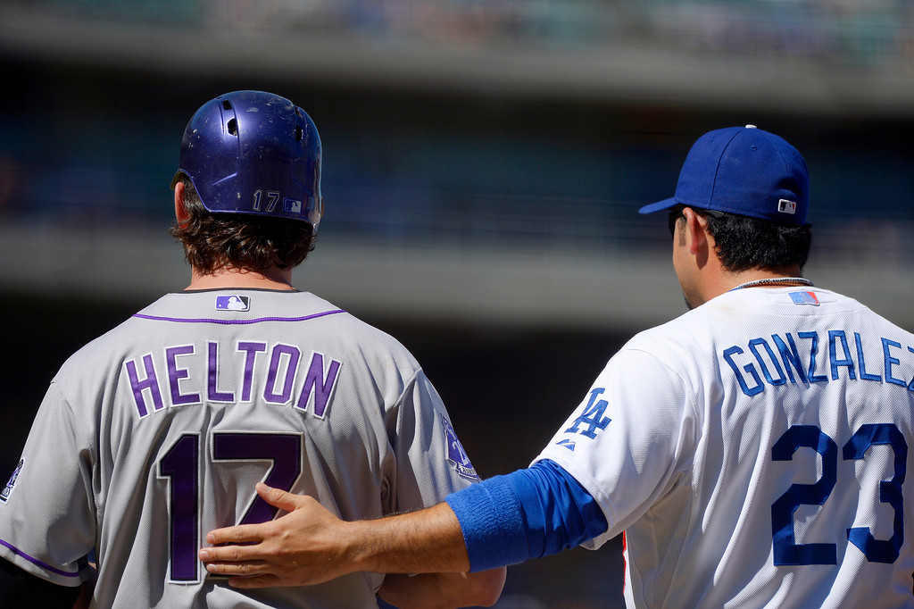 . Los Angeles Dodgers first baseman Adrian Gonzalez, right, pats Colorado Rockies\' Todd Helton on the back as Helton stands on first during the first inning of a baseball game, Sunday, Sept. 29, 2013, in Los Angeles. (AP Photo/Mark J. Terrill)