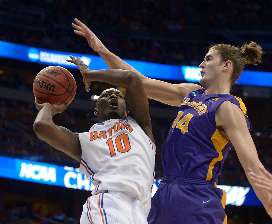 . Albany center John Puk (44) fouls Florida forward Dorian Finney-Smith (10) during the first half of a second-round game in the NCAA college basketball tournament on Thursday, March 20, 2014, in Orlando, Fla. (AP Photo/Phelan M. Ebenhack)