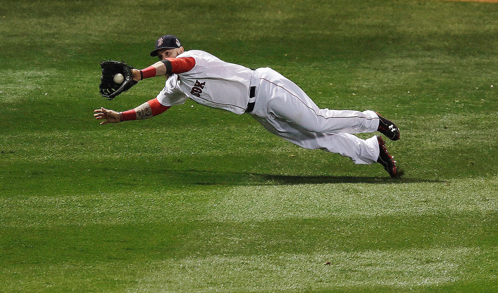 . Boston Red Sox\'s Jonny Gomes makes a diving catch on a ball hit by St. Louis Cardinals\' Matt Adams during the fifth inning of Game 1 of baseball\'s World Series Wednesday, Oct. 23, 2013, in Boston. (AP Photo/Charles Krupa)