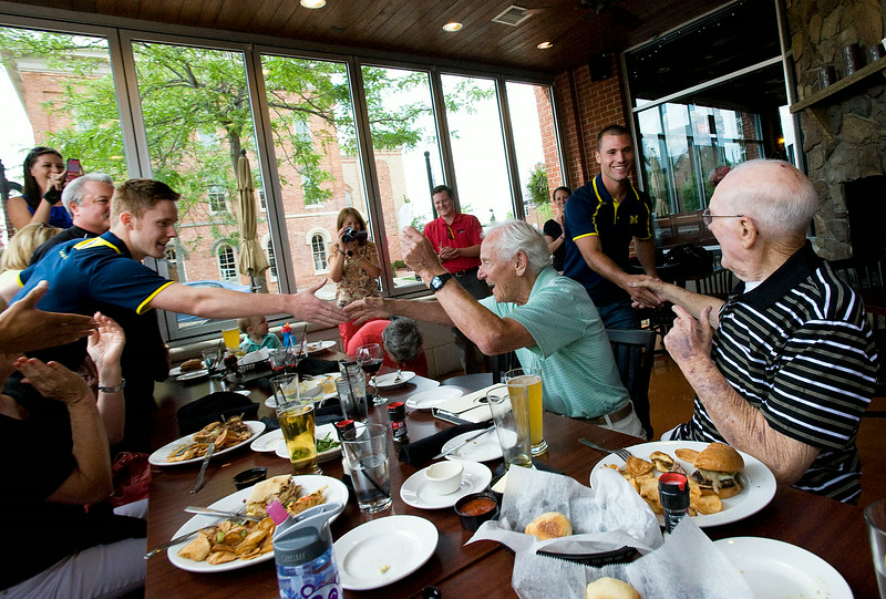 CAPTION INFORMATION Edward Gardner,85, shakes the hand of U-M soccer player James Murphy, left, and Edward's friend, Earl Linford,88, shakes U-M soccer player Tyler Arnone's hand after the two were surprised with four tickets during lunch at Main Street Crossing in Brighton on July 25, 2014.   They will get to see Manchester United play Real Madrid at U-M stadium on August 2.  (Mark Bialek / Special to the Det News)