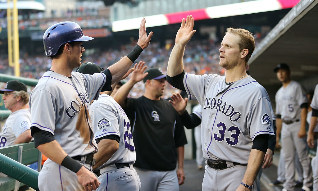 . DETROIT, MI - AUGUST 02: Drew Stubbs #13 of the Colorado Rockies celebrates with teammate Justin Morneau #33 after scoing on the fielders choice by Charlie Culberson #23 during the second inning of the game against the Detroit Tigers at Comerica Park on August 2, 2014 in Detroit, Michigan.  (Photo by Leon Halip/Getty Images)
