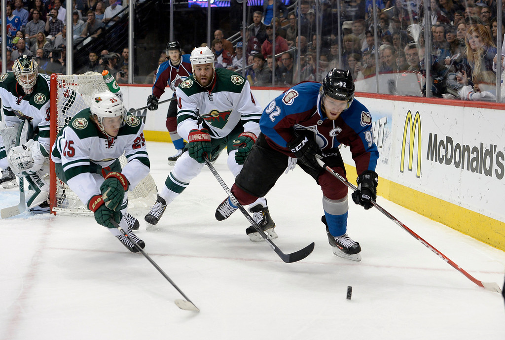 . DENVER, CO - APRIL 26: Colorado Avalanche left wing Gabriel Landeskog (92) takes the puck behind the Minnesota Wild net with Minnesota Wild defenseman Clayton Stoner (4) and Minnesota Wild defenseman Jonas Brodin (25) chasing during the first period of action. The Colorado Avalanche hosted the Minnesota Wild in the fifth round of the Stanley Cup Playoffs at the Pepsi Center in Denver, Colorado on Saturday, April 26, 2014. (Photo by John Leyba/The Denver Post)