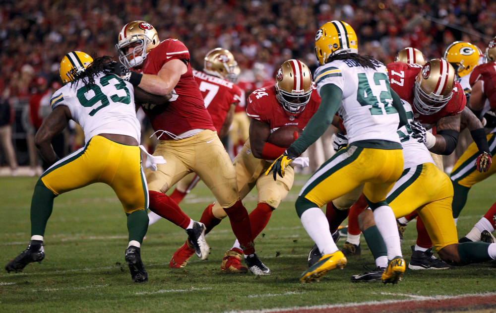 . San Francisco 49ers Anthony Dixon (C) runs past Green Bay Packers Morgan Burnett (R) to score a touchdown in the fourth quarter during their NFL NFC Divisional play-off football game in San Francisco, California January 12, 2013.  REUTERS/Robert Galbraith
