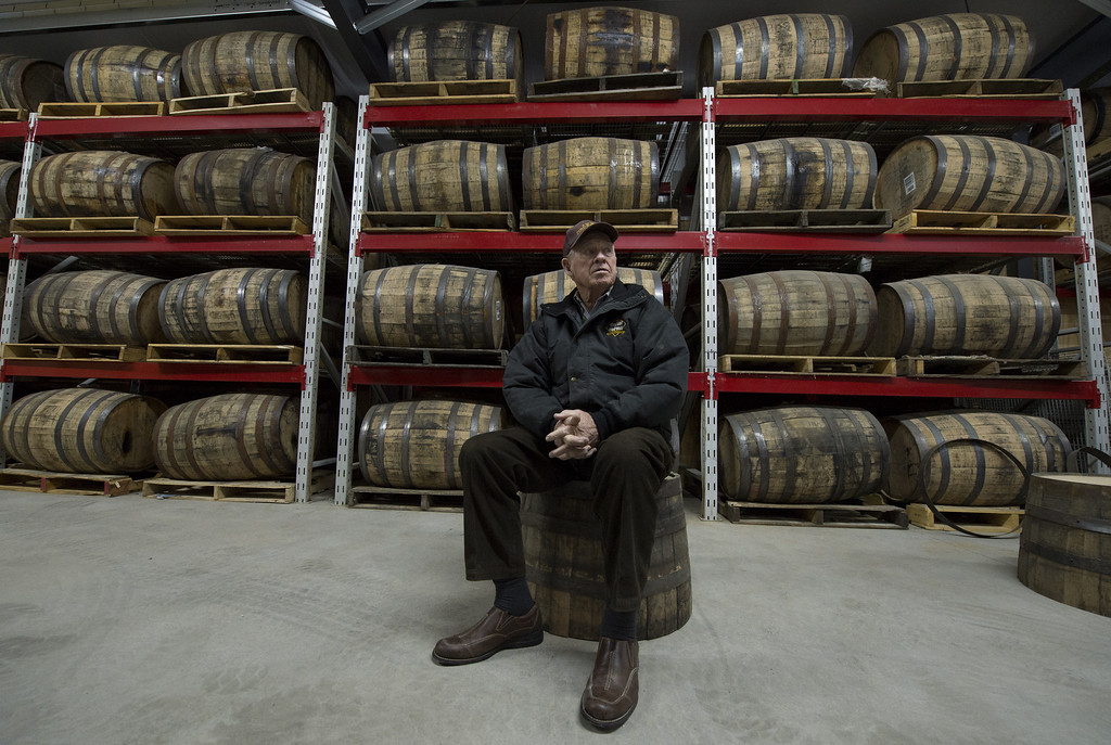 . Carlos Lovell, 85, sits in the barrel aging room for sour mash whiskey at the Ivy Mountain Distillery in Mt. Airy, Georgia, USA, 26 February 2013. The Lovell family began distilling the once illegal moonshine 150 years ago in the north Georgia mountains. Carlos and his younger brother Fred learned how to make moonshine when they were teenagers, and continued making the 95 proof spirits until the early 1960s, but now have resumed their craft legally.  EPA/ERIK S. LESSER
