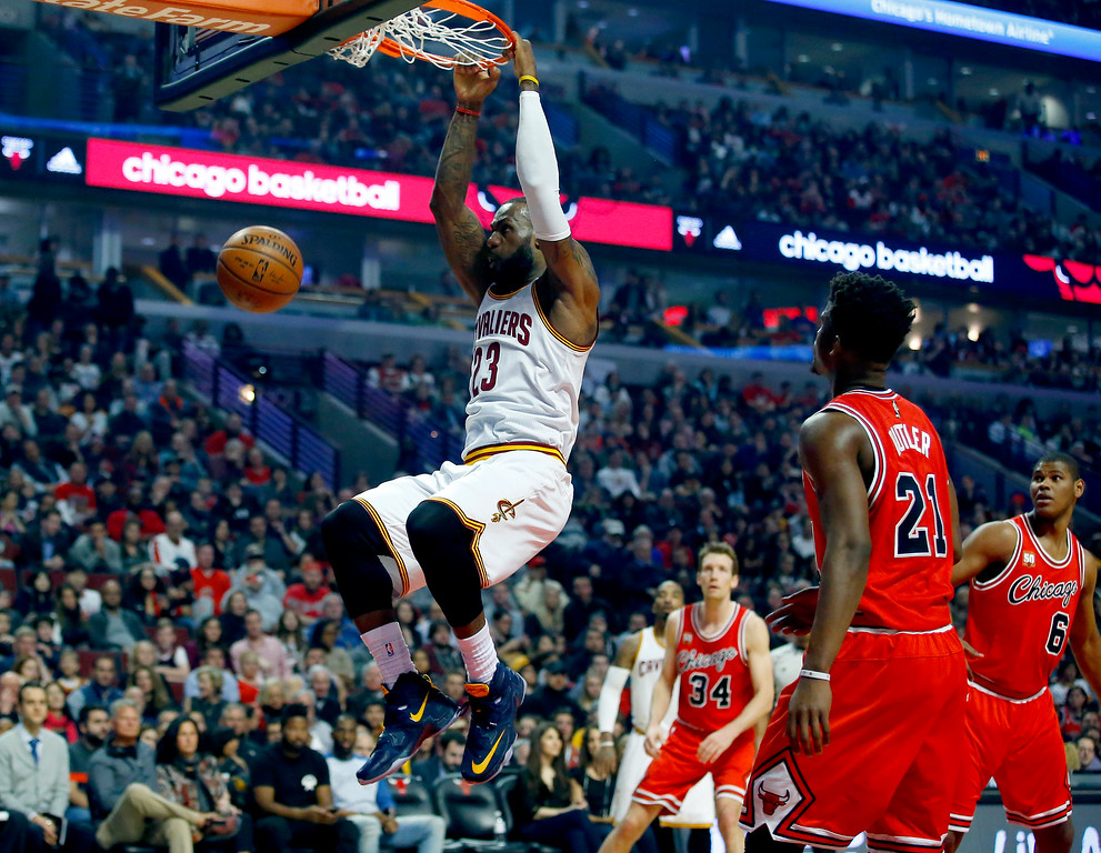 . Cleveland Cavaliers forward LeBron James (23) hangs from the rim after dunking against the Chicago Bulls during the first half of an NBA basketball game in Chicago on Saturday, April 9, 2016. (AP Photo/Jeff Haynes)
