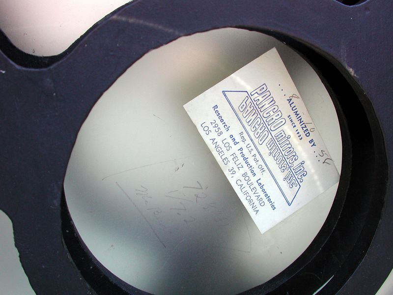 """This image taken from the back of the 10 inch primary has the date of 8-10-58 in ink on the original Pancro mirrors Inc sticker. This was the company that aluminized almost all of Caves mirrors for many years. This of course now dates the instrument of being a 1958 model. When I saw this I was """"floored"""". This telescope has the original coatings !! To my suprise they are somewhat useable  !! The mirror also has written in pencil 72 - 1/2 inches and 1/7.2, also the name Mr. Burke appears on the mirror. The original coatings combined with a clean rack and pinion focuser, finder scope and tight equatorial mount substantiate the previous owners claim that this was a barely used instrument !!"""