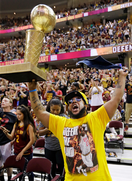 . De\'Milles Jones holds up a trophy as he cheers for the Cleveland Cavaliers during a watch party at Quicken Loans Arena during Game 5 of basketball\'s NBA Finals between the Golden State Warriors and the Cleveland Cavaliers, Monday, June 12, 2017, in Cleveland. (AP Photo/Tony Dejak)