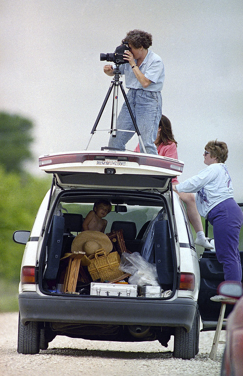 . Tourists make use of the roof of their van as a platform for a medium format camera which they were using to try for a better view of the Branch Davidian compound some three miles away in Waco, Texas on Saturday, April 18, 1993. Operating the camera is Gail Nogle of Dallas, while on ladder is Nancy Bailey of Anderson, Ind. and in van is Graham Dunlap, 3, of Dallas. (AP Photo/Rick Bowmer)