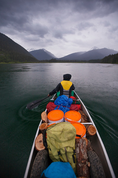 Canoeing in the rain across McLeary Lake during a multi-day canoe trip through Bowron Lake Provincial Park.