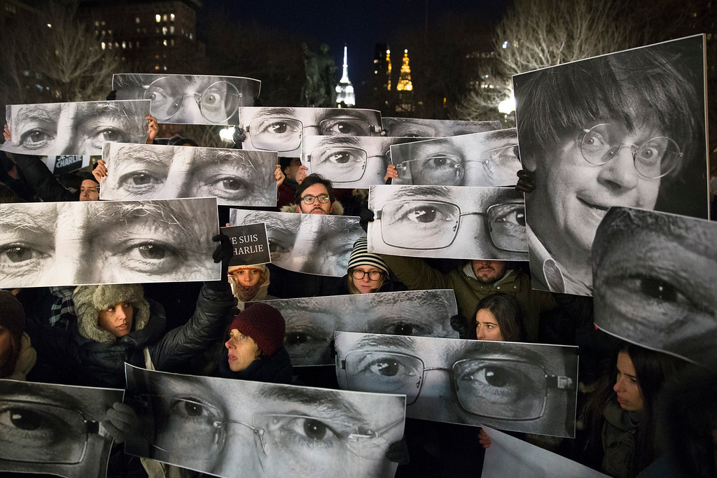 . Mourners hold signs depicting victim\'s eyes during a rally in support of Charlie Hebdo, a French satirical weekly newspaper that fell victim to an terrorist attack, Wednesday, Jan. 7, 2015, at Union Square in New York. French officials say 12 people were killed when masked gunmen stormed the Paris offices of the periodical that had caricatured the Prophet Muhammad. (AP Photo/John Minchillo)