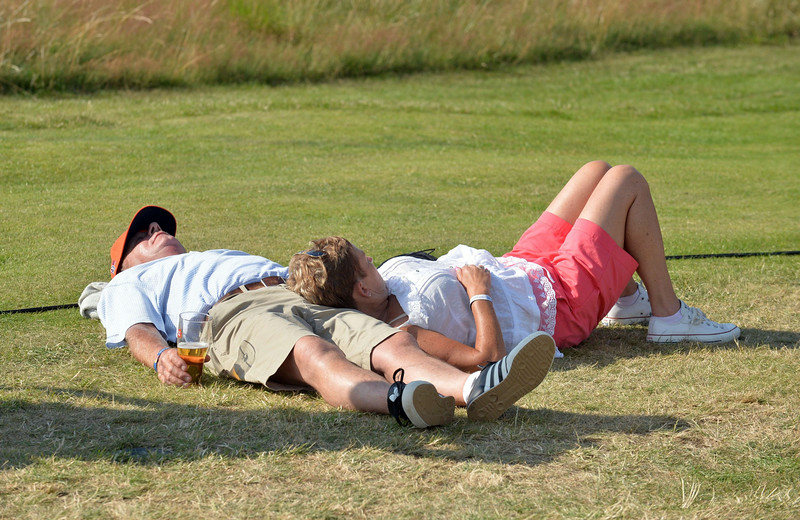 . Spectators sleep in the sunshine on the opening day of the 2014 British Open Golf Championship at Royal Liverpool Golf Course in Hoylake, north west England on July 17, 2014. (PAUL ELLIS/AFP/Getty Images)