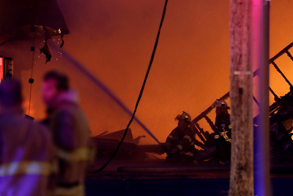 . Firefighters battle a blaze in a building at the Seaside Park boardwalk on Thursday, Sept. 12, 2013, in Seaside Park, N.J. The fire began in a frozen custard stand on the Seaside Park section of the boardwalk and quickly spread north into neighboring Seaside Heights. (AP Photo/Julio Cortez)