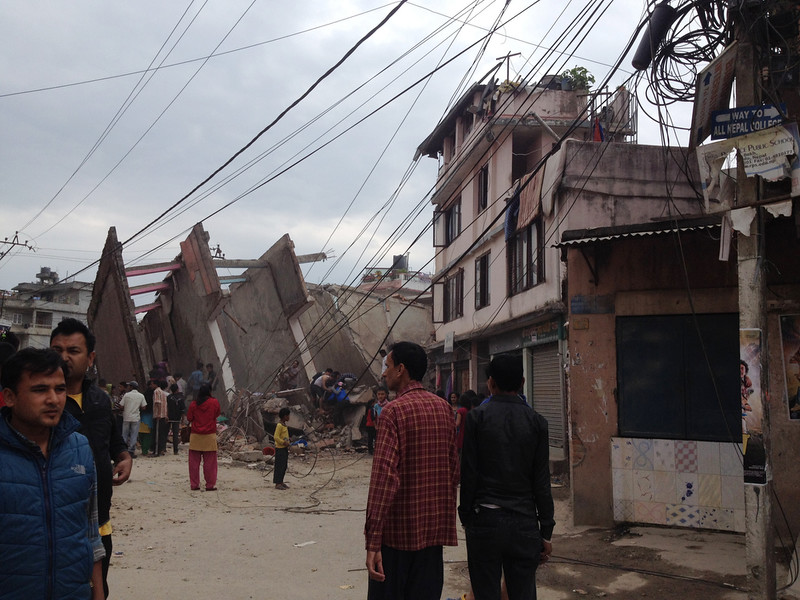 . In this photo provided by Guna Raj Luitel, people walk next to ruble after an earthquake in Kathmandu, Nepal, Saturday, April 25, 2015. A powerful earthquake shook Nepal\'s capital and the densely populated Kathmandu Valley before noon Saturday, collapsing houses, leveling centuries-old temples and cutting open roads in the worst temblor in the Himalayan nation in over 80 years. (Guna Raj Luitel via AP)