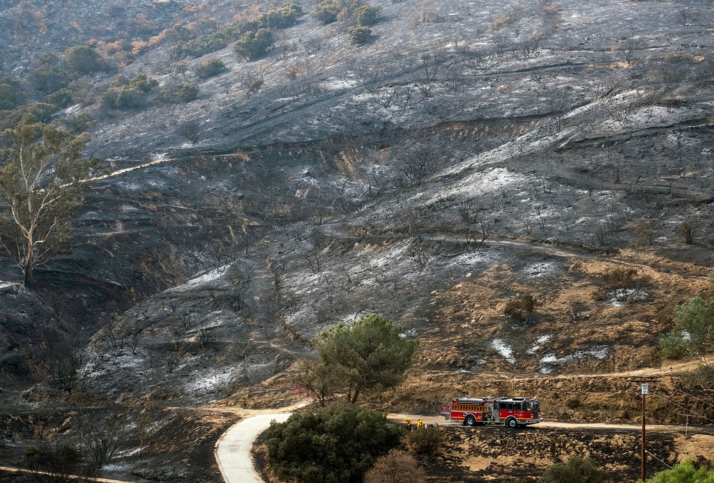 . A fire engine drives past a burned area from a wildfire Monday, Sept. 4, 2017, in the Sunland-Tujunga section of Los Angeles. (AP Photo/Ringo H.W. Chiu)