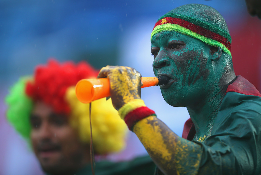 . A Cameroon fan blows a horn in the rain during the 2014 FIFA World Cup Brazil Group A match between Mexico and Cameroon at Estadio das Dunas on June 13, 2014 in Natal, Brazil.  (Photo by Clive Rose/Getty Images)