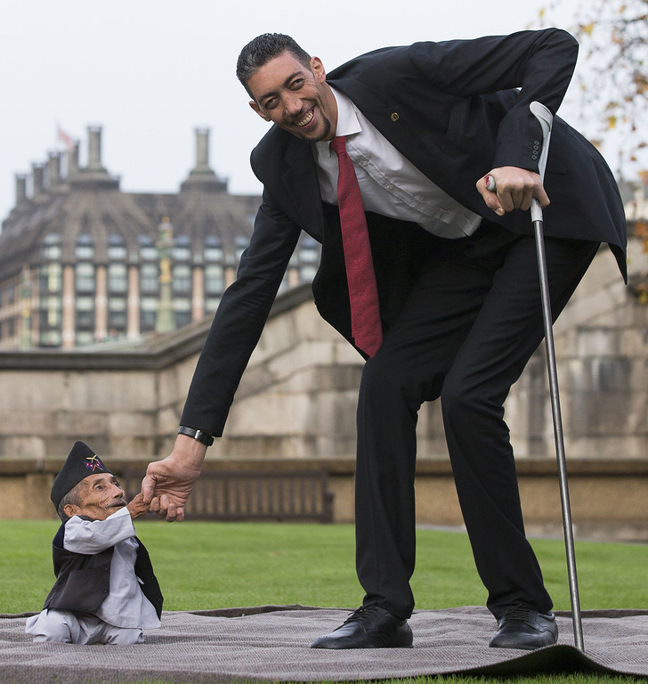 . Chandra Bahadur Dangi, from Nepal, (L) the shortest adult to have ever been verified by Guinness World Records, meets the world\'s tallest man Sultan Kosen from Turkey, during a photocall in London on November 13, 2014, to mark Guinness World Records Day. Chandra Dangi, measures a tiny 21.5in (0.54m)  the same height as six stacked cans of beans. Sultan Kosen measures 8 ft 3in (2.51m).  AFP PHOTO / ANDREW COWIE/AFP/Getty Images