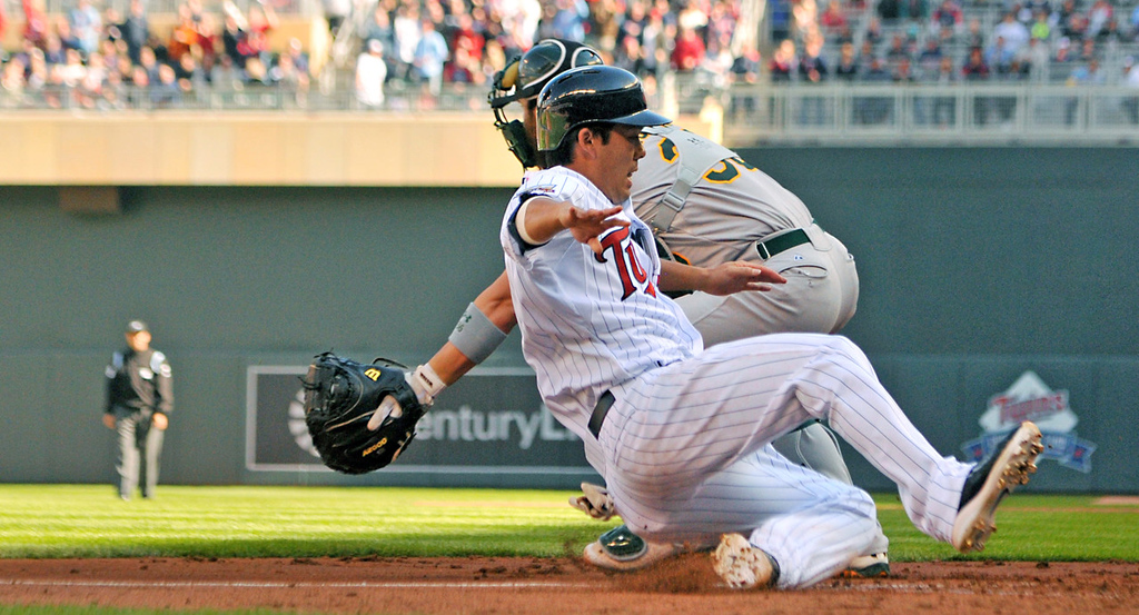 . Minnesota base runner Kurt Suzuki scores on a Aaron Hicks double as Oakland catcher Derek Norris waits for the throw in the second inning. (Pioneer Press: John Autey)