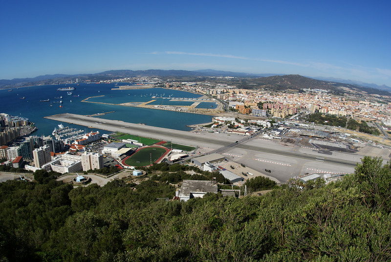 Gibraltar.  The peninsula is only 3 sq miles.  In the middle is the Gibraltar airport runway.  A 4 line highway intersects the runway so when plane are landing they lower a gate.  Everything at the top of the photo is either sky or Spain.