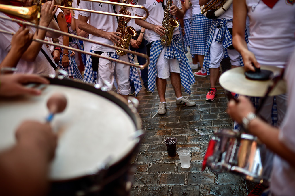 . A group of musicians play with glasses of liquor at their feet, at the San Fermin Festival in Pamplona, northern Spain, Monday, July 9, 2018. Revellers from around the world flock to Pamplona every year to take part in the eight days of the running of the bulls. (AP Photo/Alvaro Barrientos)