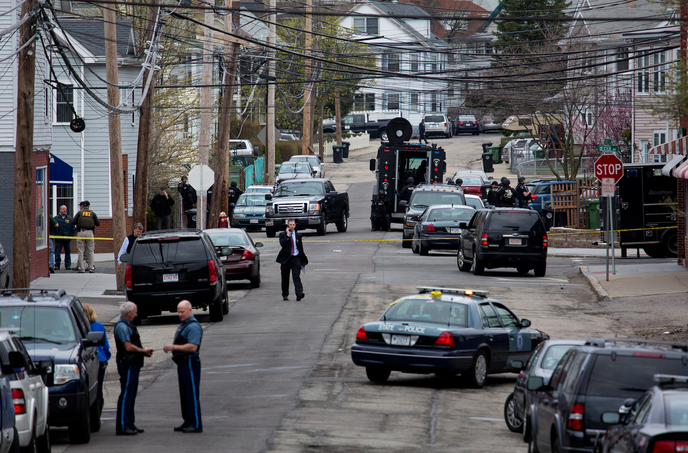 Description of . Police presence grows in the neighborhoods of Watertown, Mass., Friday, April 19, 2013, as a massive search involving hundreds of heavily armed law enforcement officials continues for one of two suspects in the Boston Marathon bombing. A second suspect died in the early morning hours in a car chase and gun battle overnight that left one of them dead and his brother on the loose, authorities said Friday. (AP Photo/Craig Ruttle)