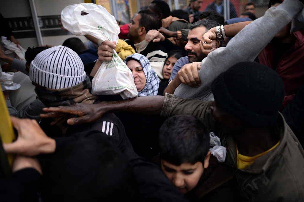 . A woman receives a bag of meat as refugees push each other during a food distribution by Bulgaria\'s chief mufti to mark the Muslim holiday of Eid al-Adha at a refugee centre in Sofia on October 17, 2013. Bulgaria said it plans to build a fence on its southeastern border with Turkey to limit the number of illegal Syrian immigrants entering the country and creating a refugee crisis. DIMITAR DILKOFF/AFP/Getty Images