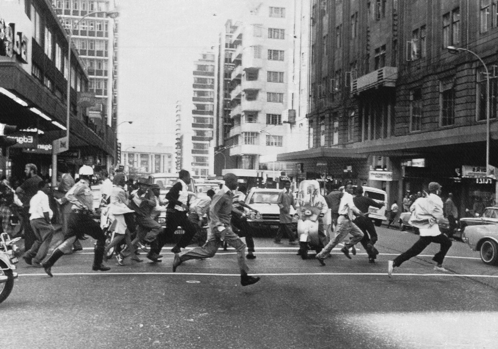 . Black youths race through the streets of Johannesburg, South Africa on Thursday, Sept. 23, 1976, fleeting police who fired shots to break up demonstrations against the government by roving mobs. In close it is a helmeted policeman, right, to have lost a leg of his action. (AP Photo)