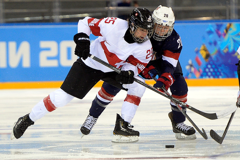 . Kendall Coyne (26) of the U.S.A. and Alina Muller (25) of the Switzerland battle for the puck during the first period of action at the Shayba Arena. Sochi 2014 Winter Olympics on Monday, February 10, 2014. (Photo by AAron Ontiveroz/The Denver Post)