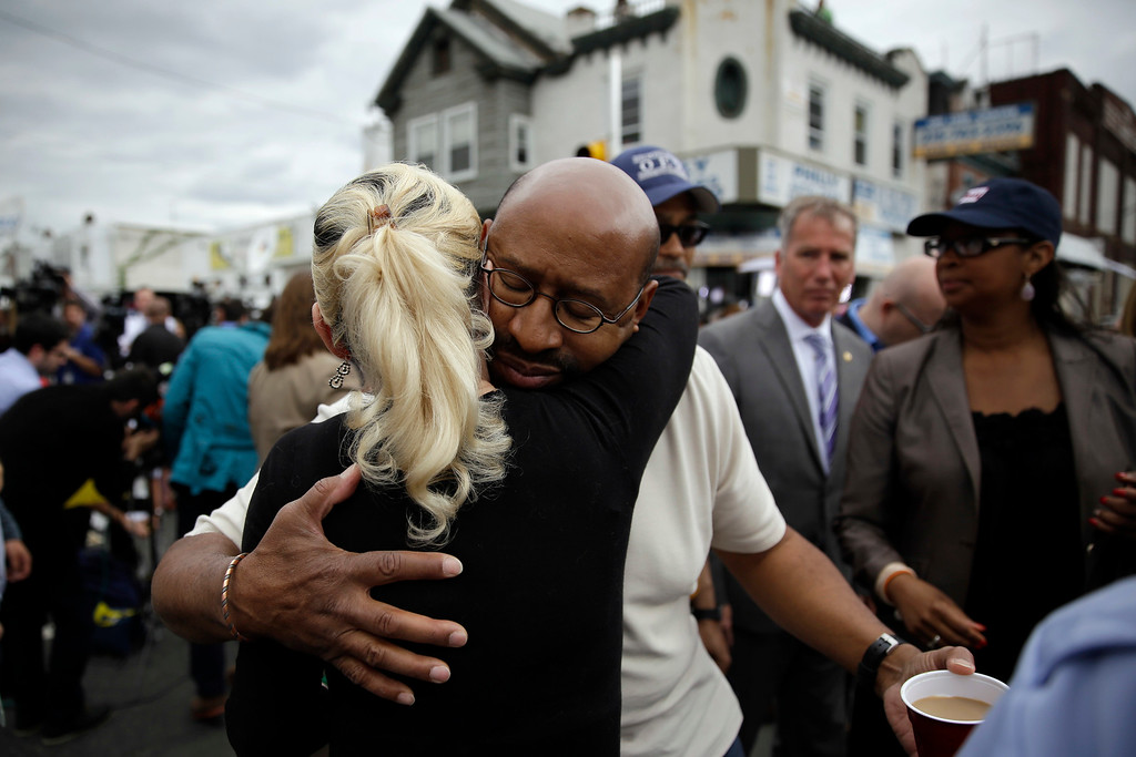 . Philadelphia Mayor Michael Nutter, center right, hugs Lori Dee Patterson, a nearby resident, after she handed him a cup of coffee after he spoke at a news conference near the scene of a deadly train derailment, Wednesday, May 13, 2015, in Philadelphia. An Amtrak train headed to New York City derailed and crashed in Philadelphia on Tuesday night, killing at least six people and injuring dozens more. (AP Photo/Matt Slocum)