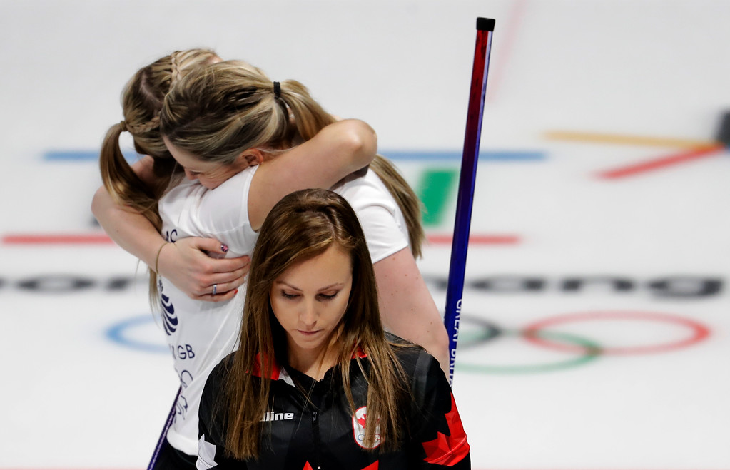 . Canada\'s skip Rachel Homan, center, leaves the ice as Britain\'s Lauren Gray, right above, and Vicki Adams embrace celebrating winning a women\'s curling match at the 2018 Winter Olympics in Gangneung, South Korea, Wednesday, Feb. 21, 2018. (AP Photo/Natacha Pisarenko)