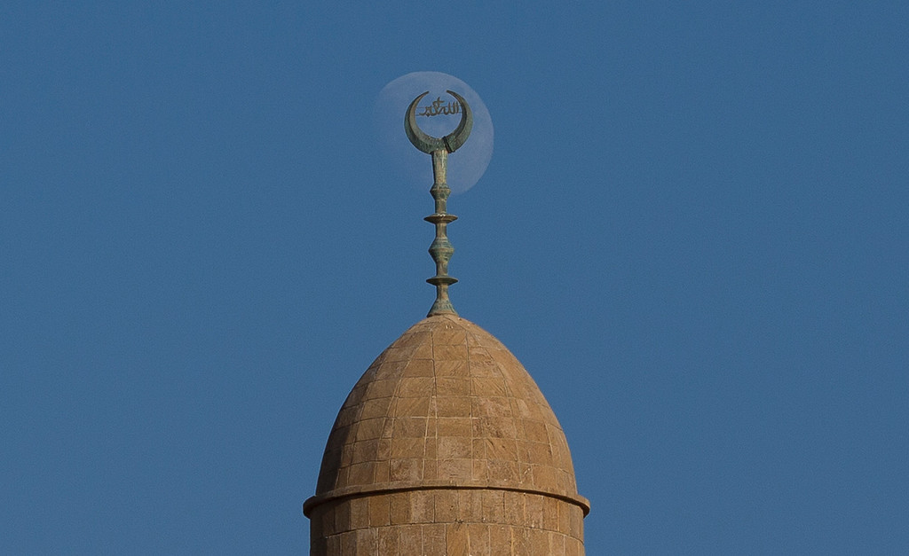 . The moon rises behind the minaret of a mosque in Jaffa, a mixed Muslim, Christian and Jewish part of Tel Aviv during the Muslim festival of Eid al-Adha , Israel, Tuesday, Oct. 15,  2013.  (AP Photo/Ariel Schalit)