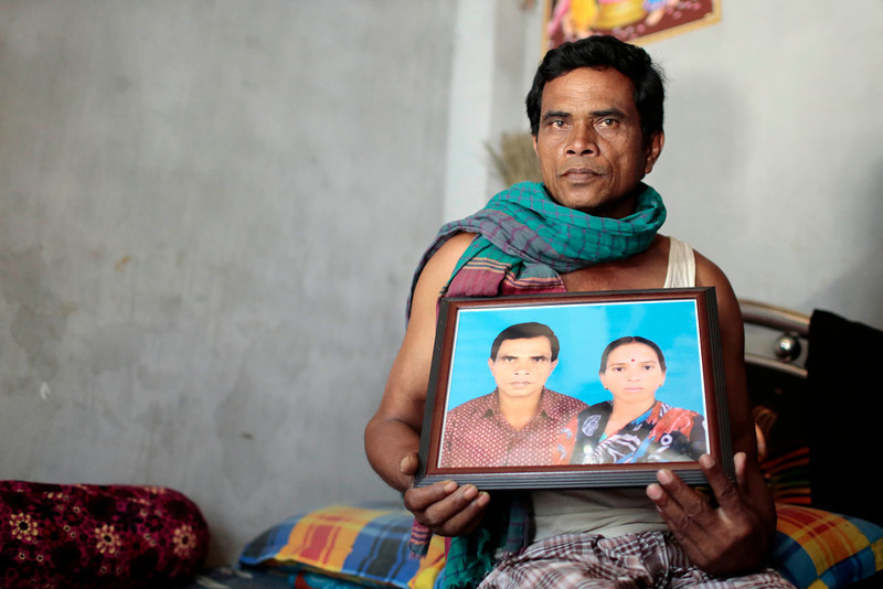 . In this Monday, April 21, 2014 photo, Bangladeshi Adhir Chondra Dash holds a portrait where he is seen with his wife Titon Bala Dash, killed in the Rana Plaza building collapse, in Savar, near Dhaka, Bangladesh. At least 1,135 people were killed when the illegally constructed, 8-story building collapsed April 24, 2013, in a heap along with thousands of workers in the five garment factories in the building. (AP Photo/A.M. Ahad)