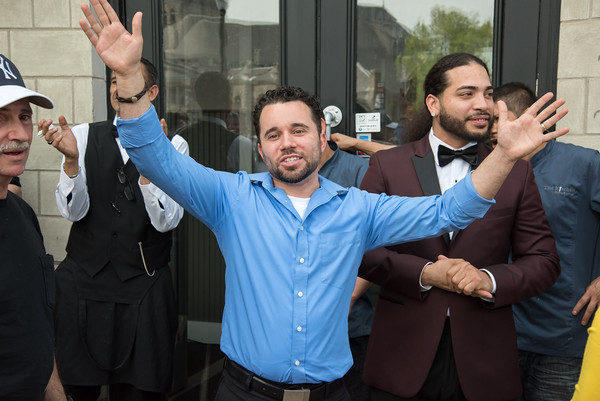 05/17/18 Wesley Bunnell | Staff Vincent Placeres held a ribbon cutting for his newest restaurant The Kitchen on Thursday afternoon down the street from Mofongo Restaurant which he opened in 2017. Placeres holds out his hands as he speaks to the crowd and invites them into the restaurant.