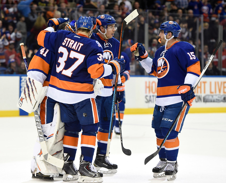 . New York Islanders goalie Jaroslav Halak (41), defenseman Brian Strait (37), defenseman Travis Hamonic (3) and right wing Cal Clutterbuck (15) celebrate their 5-4 win over the Detroit Red Wings in an NHL hockey game on Sunday, March 29, 2015, in Uniondale, N.Y. (AP Photo/Kathy Kmonicek)
