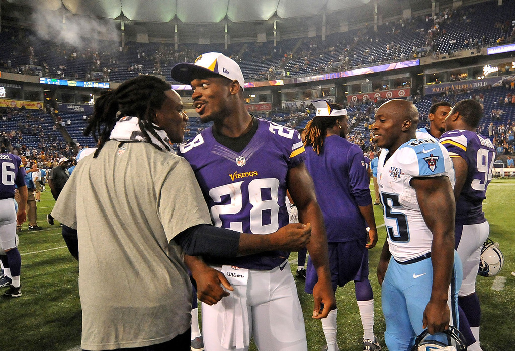 . Vikings running back Adrian Peterson, who did not play in the game, talks with Tennessee Titans running back Chris Johnson following the Vikings\' 24-23 win in their final preseason game at the Metrodome in Minneapolis on Thursday August 29, 2013.  (Pioneer Press: Sherri LaRose-Chiglo)