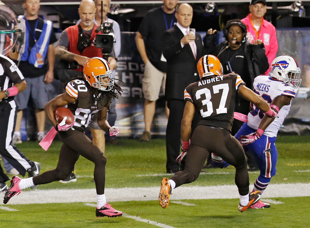 . Cleveland Browns\' Travis Benjamin (80) returns a punt 79 yards for a touchdown against the Buffalo Bills in the second quarter of an NFL football game Thursday, Oct. 3, 2013, in Cleveland. Browns\' Josh Aubrey (37) seals off Bills\' Jonathan Meeks to spring Richardson. (AP Photo/Tony Dejak)