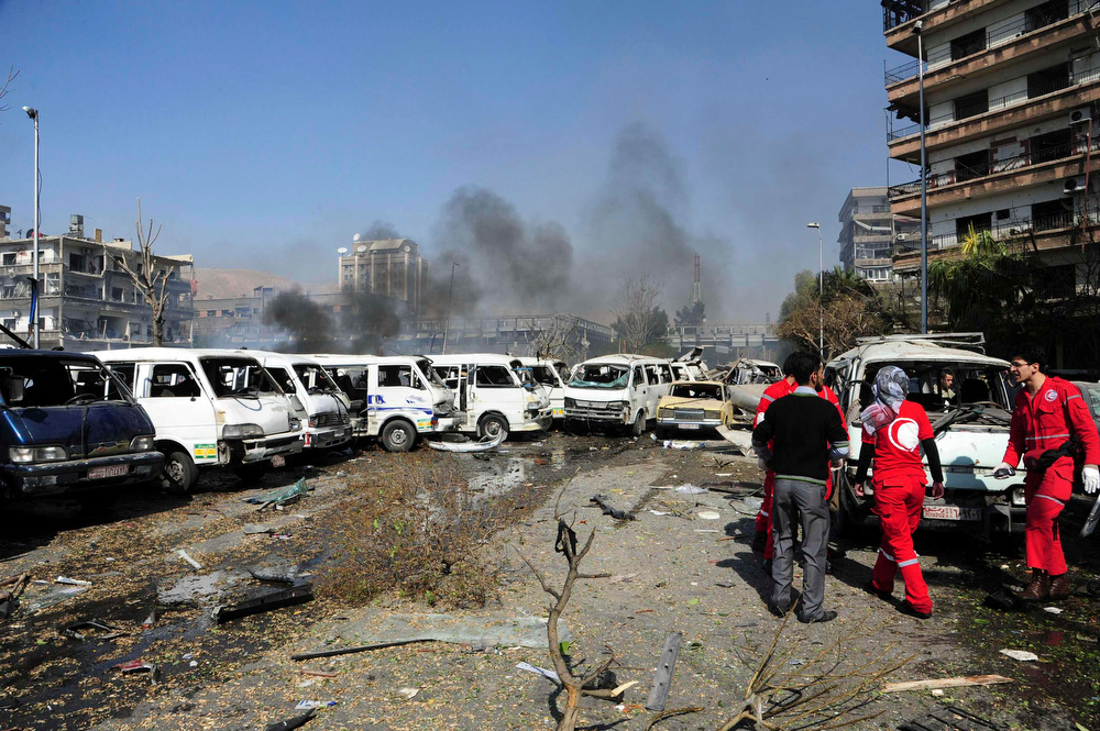Description of . Damaged vehicles and the Russian embassy building (rear C) are seen after an explosion in central Damascus February 21, 2013, in this handout photograph released by Syria's national news agency SANA. A car bomb killed 53 people and wounded 200 in central Damascus on Thursday when it blew up on a busy highway close to ruling Baath Party offices and the Russian Embassy, Syrian television said. REUTERS/Sana