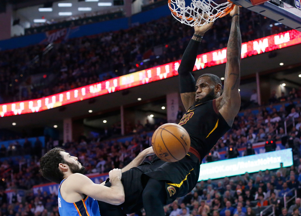 . Cleveland Cavaliers forward LeBron James hangs from the basket after dunking in front of Oklahoma City Thunder guard Alex Abrines during the first half of an NBA basketball game in Oklahoma City, Tuesday, Feb. 13, 2018. (AP Photo/Sue Ogrocki)