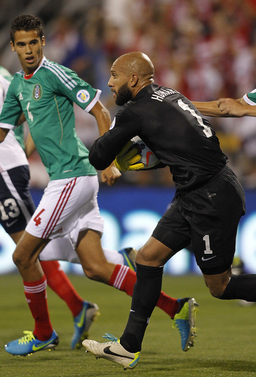 . Tim Howard of USA (R) makes a stop in front of Diego Reyes of Mexico during the first half of their Brazil 2014 FIFA World Cup qualifier at Columbus Crew Stadium in Columbus, Ohio, September 10, 2013.   AFP PHOTO / PAUL VERNONPaul VERNON/AFP/Getty Images