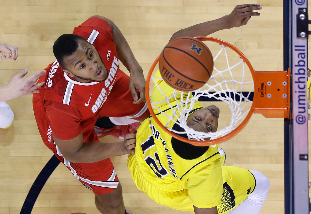 . Michigan guard Muhammad-Ali Abdur-Rahkman (12) and Ohio State center Trey McDonald watch as a shot by Ohio State guard D\'Angelo Russell goes into the basket during the first half of an NCAA college basketball game, Sunday, Feb. 22, 2015, in Ann Arbor, Mich. Michigan defeated Ohio State 64-57. (AP Photo/Carlos Osorio)